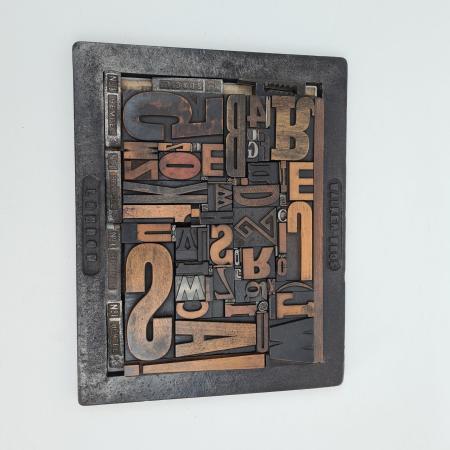 Collage aus Holzlettern mit Setzrahmen aus Metall